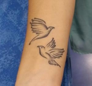Tatuaje de dos palomas en muñeca