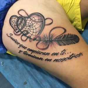 Tatuaje de pluma y corazones con frase tipográfica