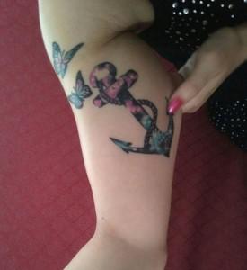 Tatuaje de ancla y mariposas de colores en brazo