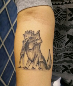 Tatuaje en brazo de niño con lobo