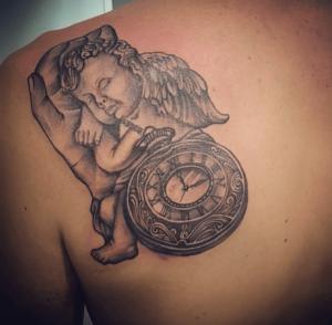 Tatuaje de ángel y reloj realizado en nuestro centro de Vaguada de Madrid